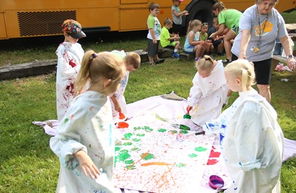 Winn students paint on giant canvas outside.